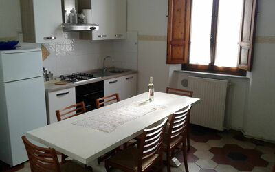 Villa Ricordi: Full kitchen on the first floor, equipped with everything you need. It includes a solid wood table with 8 chairs, a small sofa and a pantry. There is also a color TV