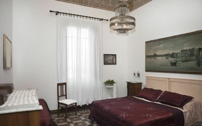 Villa Ricordi: Double room with vaulted ceiling, large wardrobe and solid wood sideboard with mirror. Two bedside tables with light on the sides of the bed. At the head of the bed a large original painting by a local author with a hunting scene ...